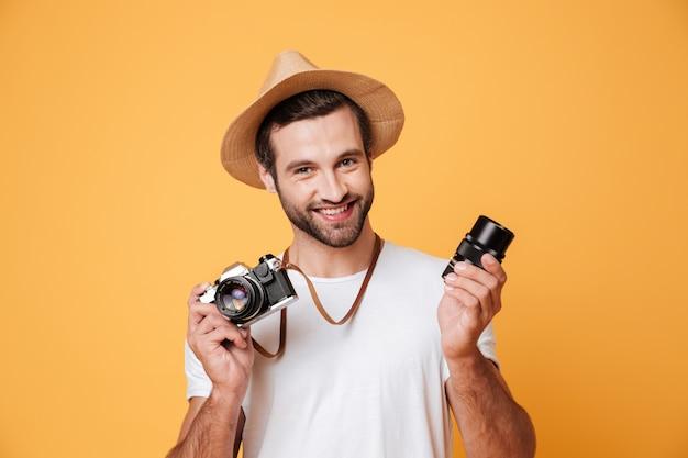 Junger lächelnder mann, der kamera schaut, während linse hält
