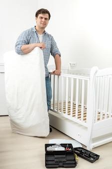 Junger lächelnder mann, der mit matratze am bett des zerlegten babys steht