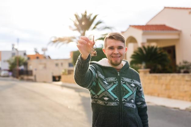 Junger lächelnder mann, der schlüssel zum neuen hausimmobilien-wohnungs- und leutekonzept zeigt
