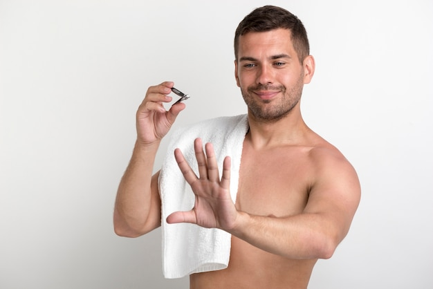 Junger lächelnder mann, der seine hand schaut, nachdem fingernägel geschnitten worden sind