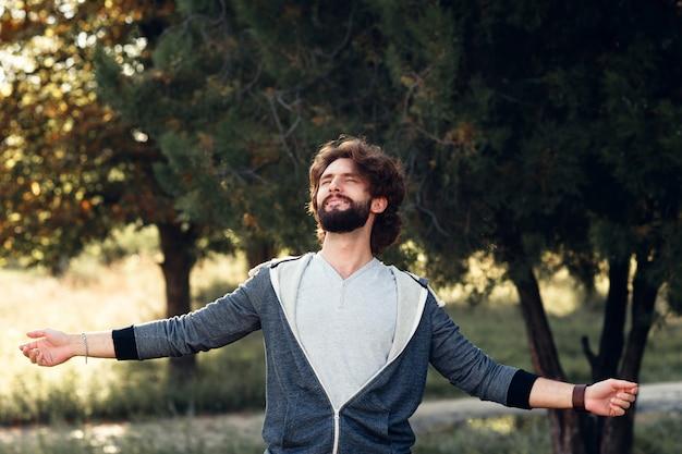 Junger lächelnder mann, der umwelt genießt