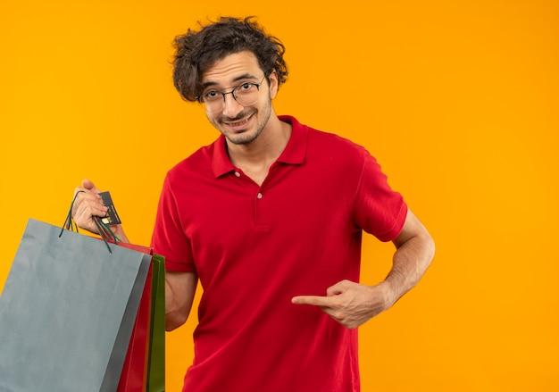 Junger lächelnder mann im roten hemd mit optischen gläsern hält und zeigt auf papiertüten lokalisiert auf orange wand