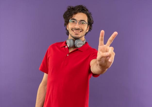 Junger lächelnder mann im roten hemd mit optischer brille und mit kopfhörern gestikuliert siegeshandzeichen lokalisiert auf violetter wand