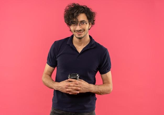 Junger lächelnder mann im schwarzen hemd mit optischen gläsern hält kaffeetasse und schaut lokalisiert auf rosa wand