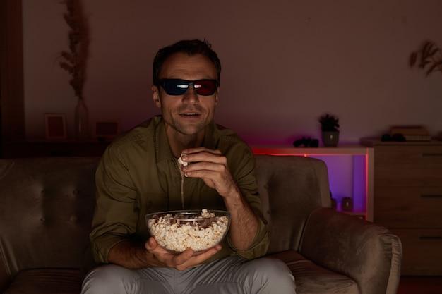 Junger lächelnder mann in 3d-gläsern, die auf sofa sitzen, popcorn essen und 3d-film zu hause ansehen