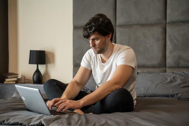 Junger lächelnder mann in einem weißen t-shirt sitzt im bett und arbeitet an einem laptop, der zu hause freiberuflich tätig ist