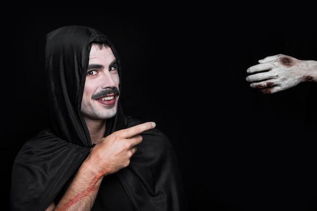 Junger lächelnder mann in halloween-kostüm zeigend auf leichnamhand