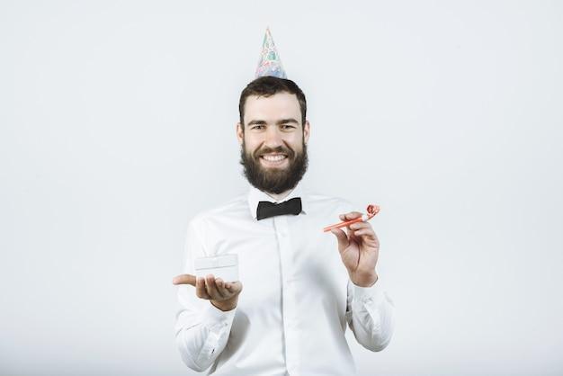 Junger lächelnder mann mit einem bart in einem cockpit, fliege in einem konischen partyhut hält ein geschenk und ein horn in seiner hand