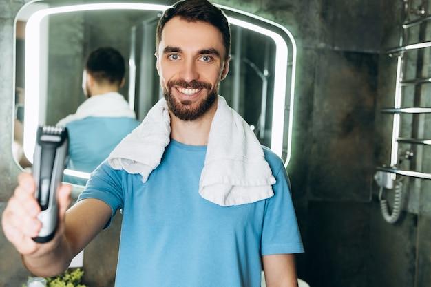 Junger lächelnder mann mit handtuch, der früh morgens im badezimmer einen brandneuen rasierer präsentiert