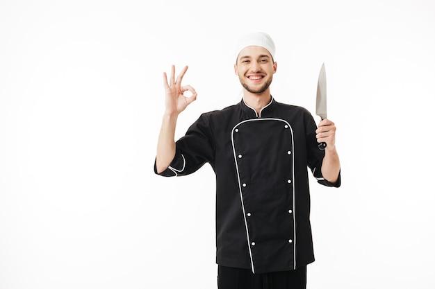 Junger lächelnder mannkoch in der schwarzen uniform, die messer in der hand glücklich hält