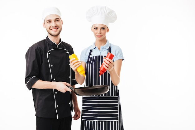 Junger lächelnder mannkoch in der schwarzen uniform, die pfanne in den händen hält, während frau in gestreifter schürze flaschen des ketchups und des senfs hält, während glücklich