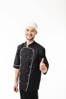 Junger lächelnder mannkoch in der schwarzen uniform freudig