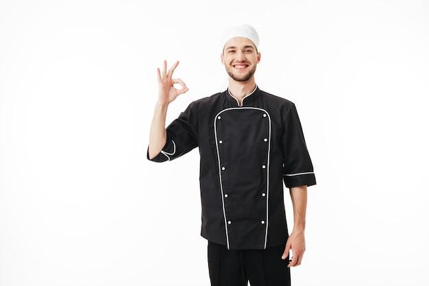 Junger lächelnder mannkoch in der schwarzen uniform glücklich