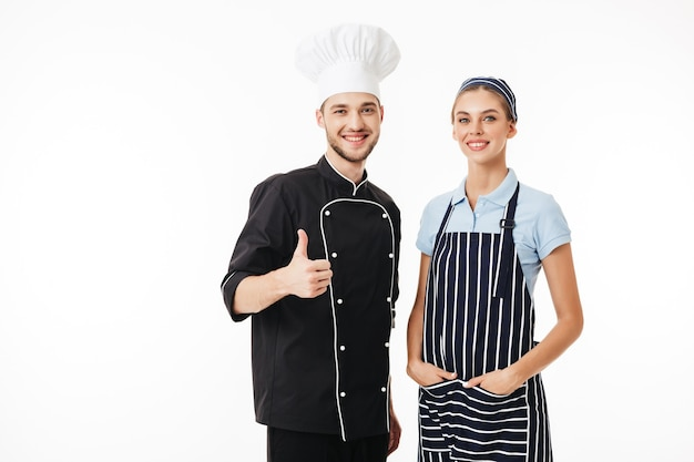 Junger lächelnder mannkoch in der schwarzen uniform und im weißen hut und in der schönen frau kochen in gestreifter schürze und mütze glücklich
