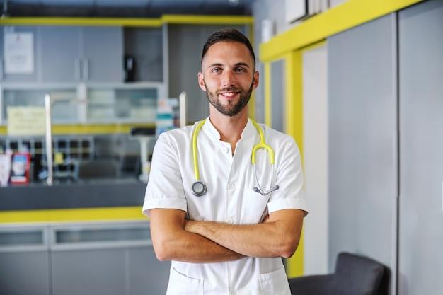 Junger lächelnder positiver bärtiger arzt, der im krankenhaus mit verschränkten armen steht