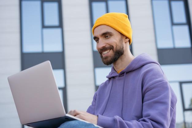 Junger lächelnder programmierer, der laptop-computer verwendet, der draußen arbeitet