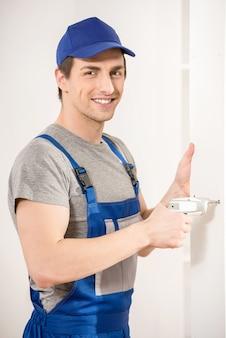 Junger lächelnder schlosser, der zu hause innenraum der handbohrmaschine verwendet.