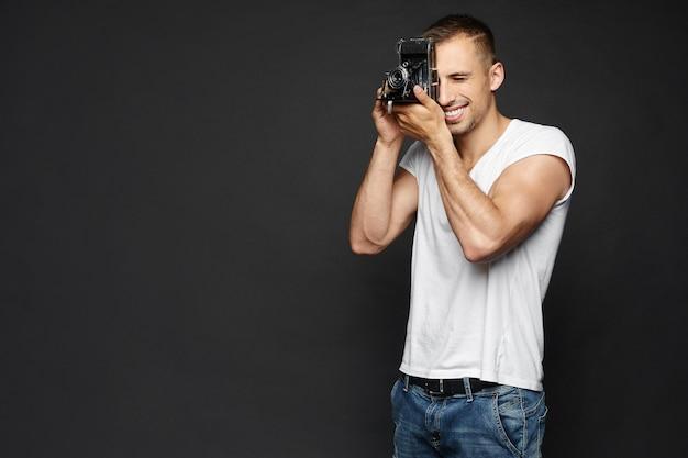 Junger lächelnder schöner mann, der eine weinlesekamera hält und ein fotoshooting macht, lokalisiert an der dunklen wand