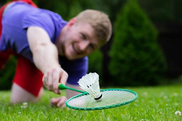 Junger lächelnder starker sportmann, der badminton mit schläger und federball spielt. fit männlicher athlet badmintonspieler fliegt über gras in sprung, aktion, bewegung, bewegung. angriffs- und verteidigungskonzept