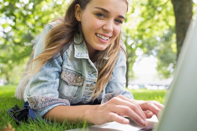 Junger lächelnder student, der auf dem gras unter verwendung des laptops liegt