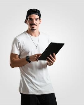 Junger lächelnder und überzeugter rappermann, eine tablette halten und verwenden, um das internet zu surfen und soziale netzwerke zu sehen, kommunikationskonzept