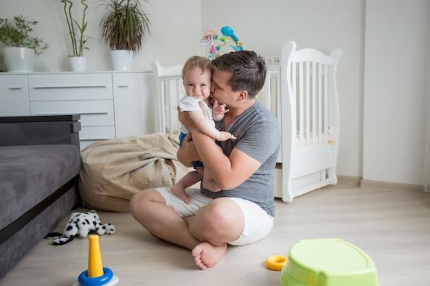 Junger lächelnder vater, der spaß mit seinem babyboden auf dem boden im schlafzimmer hat