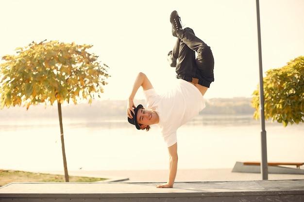Junger lässiger mann, der draußen im stadtpark tanzt