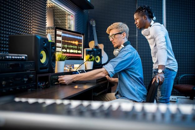 Junger lässiger mann, der volumen hinzufügt, während musik mit seinem afrikanischen kollegen im zeitgenössischen studio aufzeichnet