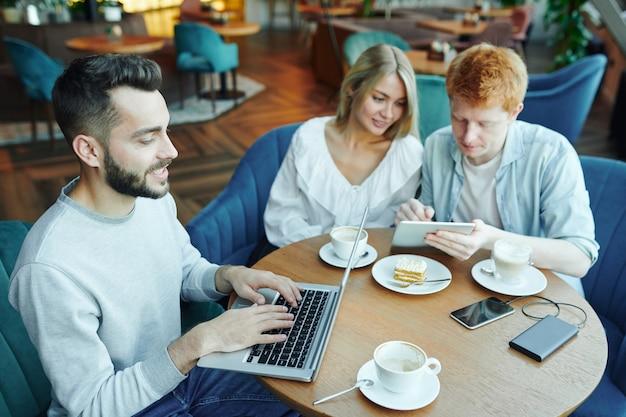 Junger lässiger mann, der vor laptop vernetzt, während seine freunde touchpad durch tasse kaffee in der nähe verwenden