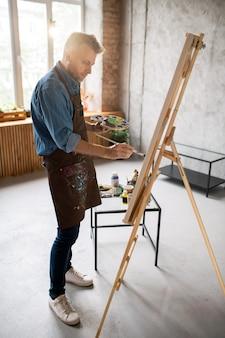 Junger lässiger mann in der schürze, die vor staffelei im atelier der künste steht und mit wasserfarben malt