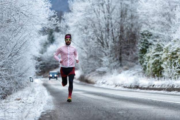 Junger läufer auf eiskalter straße auf den alpen