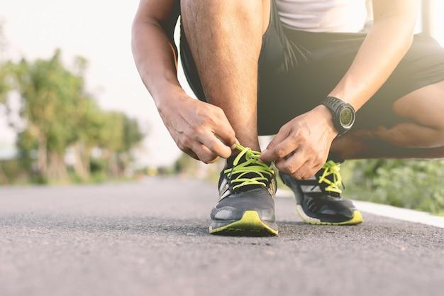 Junger läufer bindet die schnürsenkel auf dem laufsteg