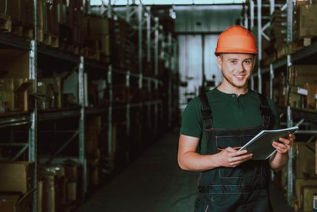 Junger lagerarbeiter im hardhat mit notizbuch