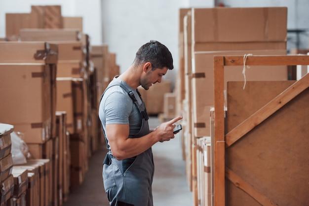 Junger lagerarbeiter in uniform steht und benutzt sein telefon.
