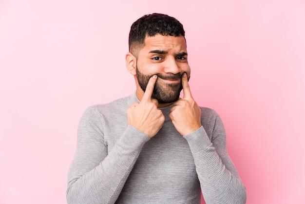 Junger lateinamerikanischer mann auf einem rosa isolierten zweifel zwischen zwei optionen.