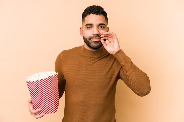 Junger lateinamerikanischer mann, der ein popcorn mit den fingern auf den lippen hält, die ein geheimnis halten.