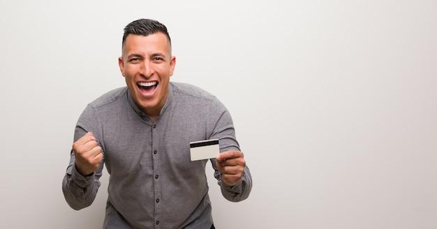 Junger lateinamerikanischer mann, der eine kreditkarte hält, überrascht und schockiert