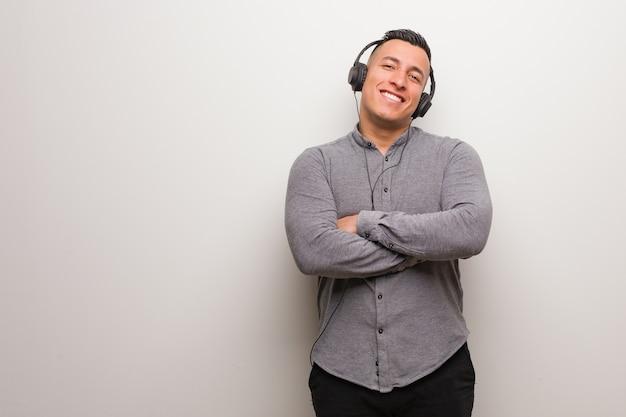 Junger lateinamerikanischer mann, der musik hört, die zuversichtlich lächelt und arme kreuzt und nach oben schaut