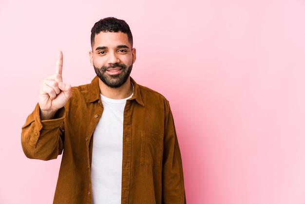 Junger lateinamerikanischer mann gegen eine rosa wand lokalisiert, die nummer eins mit finger zeigt.