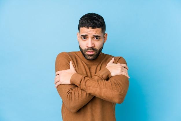 Junger lateinamerikanischer mann gegen einen blauen hintergrund isoliert, der wegen niedriger temperatur oder einer krankheit kalt wird.