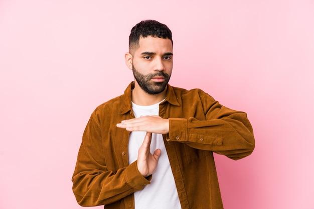 Junger lateinamerikanischer mann gegen einen rosa isolierten, der eine zeitüberschreitungsgeste zeigt.
