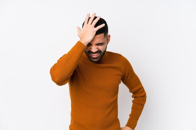 Junger lateinamerikanischer mann gegen einen weißen isolierten, der etwas vergisst, stirn mit handfläche schlägt und augen schließt.