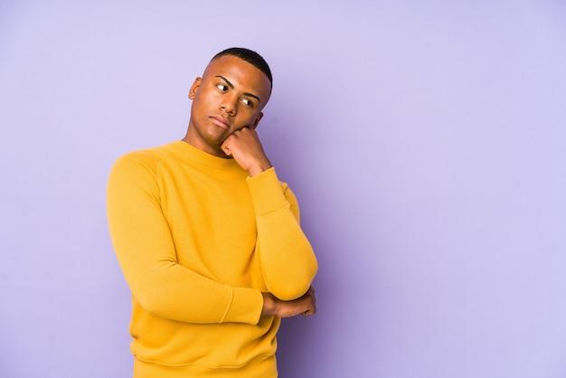 Junger lateinamerikanischer mann lokalisiert auf purpur, der sich traurig und nachdenklich fühlt und kopierraum betrachtet.
