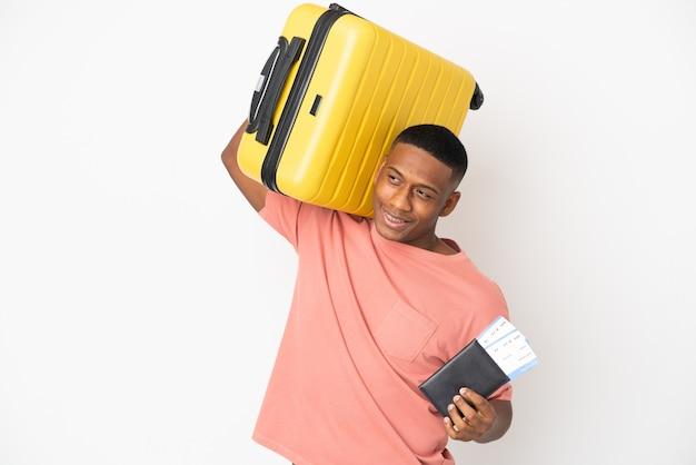 Junger lateinamerikanischer mann lokalisiert auf weißem hintergrund im urlaub mit koffer und pass