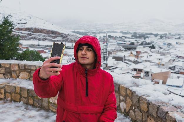 Junger lateinamerikanischer mann macht ein selfie in einer verschneiten stadt