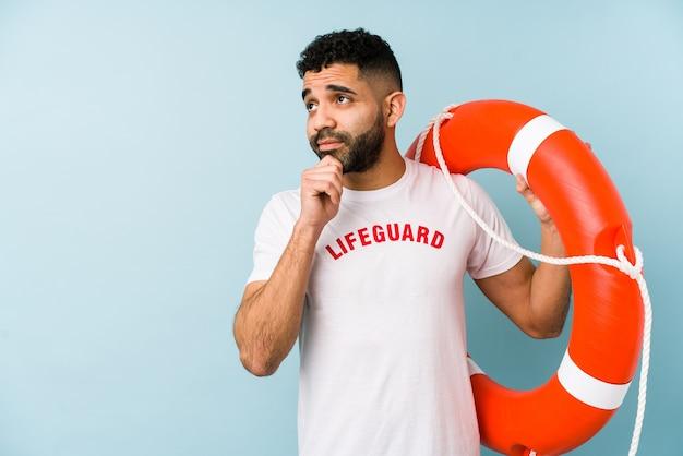 Junger lateinamerikanischer rettungsschwimmermann, der seitlich mit zweifelhaftem und skeptischem ausdruck schaut.