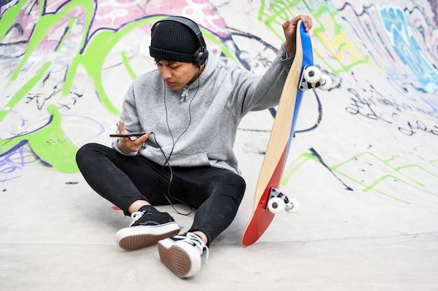Junger lateinamerikanischer skatermann, der mit skateboard am skatepark aufwirft.