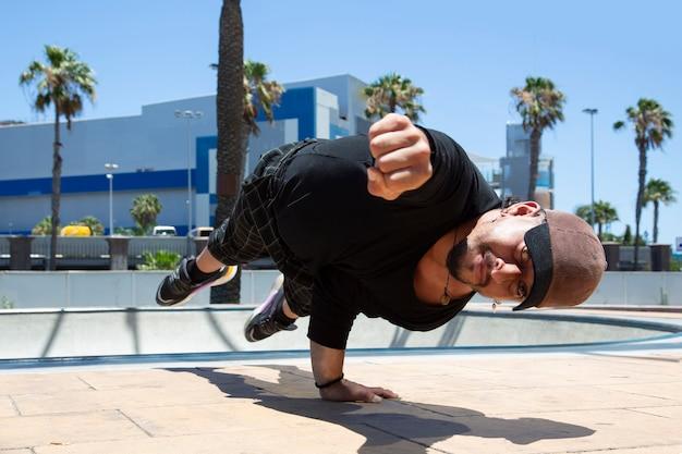 Junger lateinamerikanischer städtischer akrobatischer tänzer auf der straße, der eine aufführung macht.
