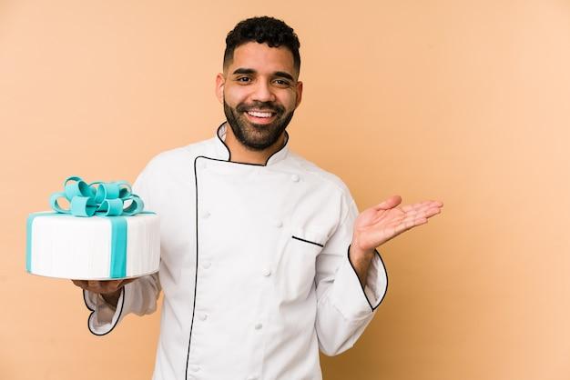 Junger lateinischer bäckermann, der einen kuchen hält, der etwas zeigt