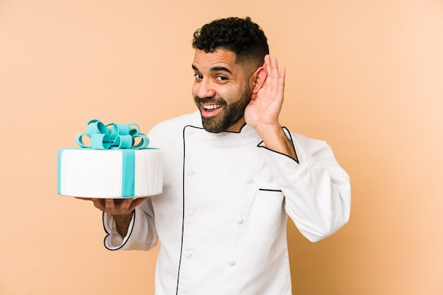Junger lateinischer bäckermann, der einen kuchen hält, der versucht, einen klatsch zu hören.